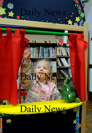 Amesbury:<br /> Casey Metcalf, almost 3, opens the stage curtains as she gets ready to do a small puppet show for her mother, Christine. The two were in the Children's Room at the Amesbury Public Library on Thursday morning.<br /> Photo by Bryan Eaton/Newburyport Daily News Thursday, February 19, 2009