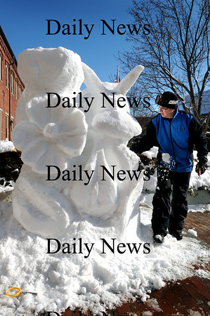 Amesbury:<br /> Sean Fitzpatrick of Saugus carves out a block of compressed snow into a sculpture of a hummingbird in a bunch of flowers, one of four he's creating in Amesbury's Upper Millyard. Flatbreads owner Jay Gould hired Fitzpatrick to capitalize on the season's excess of snow.<br /> Photo by Bryan Eaton/Newburyport Daily News Wednesday, February 04, 2009