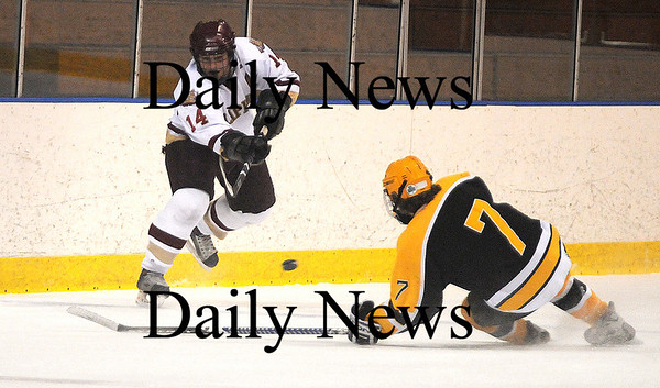 Salem: Newburyport's David Freeman passes the puck over Bishop Fenwick's Mike Cipriani during the Cippers 4-3 victory Tuesday night at Salem State College. photo by Jim Vaiknoras