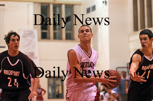 Amesbury: David Miller (22) of Amesbury drives past two Rockport defenders during Monday night's game at AHS. Photo by Ben Laing/Newburyport Daily News Monday January 12, 2009.
