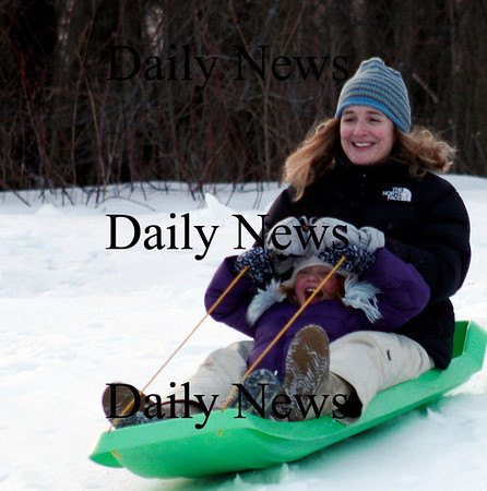 Newburyport: Morgan Mead and her mom, Christine, of Newbury, race down March's Hill in Newburyport Thursday afternoon. The three propellers of the new windmill have been assembled and the hub now just needs to be lifted into place. Work was postponed Thursday due to the wind. Photo by Ben Laing/Newburyport Daily News Thursday January 8, 2009.