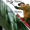 Amesbury:<br /> With temperatures above freezing and the back of a hammer, hired hand John Walton breaks up icicles and ice off the roof of a downtown office building in Amesbury on Friday. The short rise in temperatures won't last as the air gets frigid again tonight into Tuesday.<br /> Photo by Bryan Eaton/Newburyport Daily News Friday, January 23, 2009