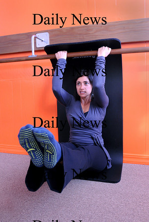 """Newburyport:<br /> Amanda Mulholland of A to Z Method demonstrates """"flat back"""" which helps with abdominal muscles.<br /> Photo by Bryan Eaton/Newburyport Daily News Friday, January 09, 2009"""