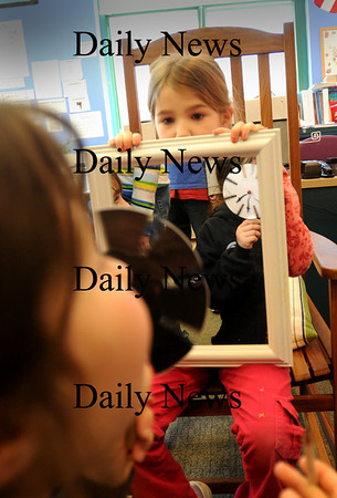 "Newbury:<br /> Morgan Dexter holds a mirror as Suzanne Kilty, both 9, looks through a phenikistoscope, which creates optical illusions through the spinning wheel with slits, at Newbury Elementary School. They were at ""Camp Newbury"" learning about life in the 1800's from staff at Historic New England.<br /> Photo by Bryan Eaton/Newburyport Daily News Tuesday, January 27, 2009"