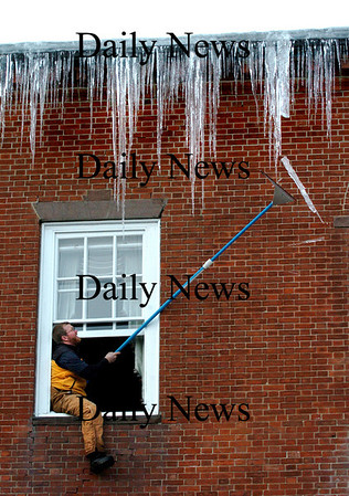 Newburyport:<br /> Mark Clevesy knocks icicles hanging above the Phoenix Room on State Street in Newburyport as the warming and cooling temperatures created a hazardous condition.<br /> Photo by Bryan Eaton/Newburyport Daily News Tuesday, January 20, 2009