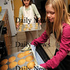 Newburyport:<br /> Molly Balentine, 7, left, has cookie dough to go into the oven as her friend Maggie Budzyna, 8, takes some out finished chocolate chip cookies. Maggie is selling cookies to help raise funds for the North Shore Music Center which is in financial difficulty.<br /> Photo by Bryan Eaton/Newburyport Daily News Thursday, January 15, 2009