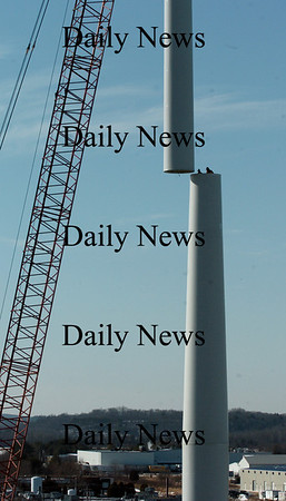 Newburyport:<br /> Two workers poke out of the top of the second section of the huge wind turbine being erected at Mark Richey Woodworking in Newburyport's industrial park, as the third section is ready to be set atop.<br /> Photo by Bryan Eaton/Newburyport Daily News Tuesday, January 06, 2009