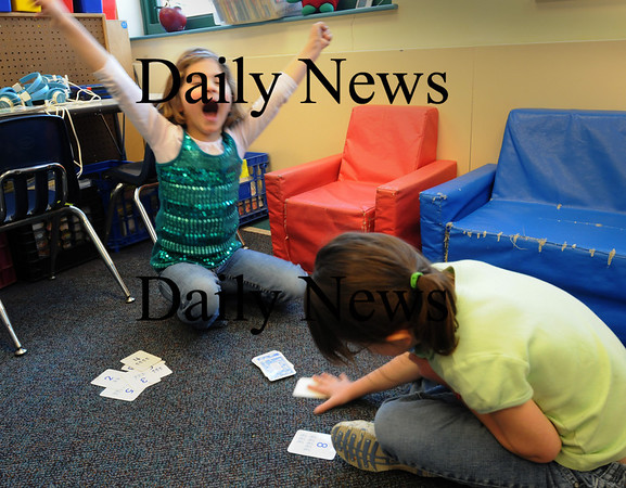 Newbury:<br /> Kate Taylor celebrates as she beats Dani White, both 6, in a hand of Compare in Nancy Mackinney's class at Newbury Elementary School on Thursday. The game, which helps with math skills, is like the card game War. In this case whoever gets the lowest numbered card in a hand wins that hand, and whoever ends up with the most cards wins.<br /> Photo by Bryan Eaton/Newburyport Daily News Thursday, January 15, 2009