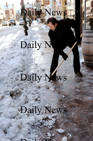 Newburyport: Jeremy Kirkpatrick or Grand Trunk cheese shop on Pleasant Street in Newburyport chips away in front  of his shop Thursday morning after the storm, which turned to rain, froze over. Many people were observed walking in the streets as some parts of sidewalks were glare ice until the sun strengthened and cleanup efforts increased as the day went on. Photo by Bryan Eaton/ Newburyport Daily News   Thursday January 29, 2008.