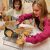 Newburyport:<br /> Molly Balentine, 7, left, helps her friend Maggie Budzyna, 8, put chocolate chip cookied on a cooling rack. Maggie is selling cookies to help raise funds for the North Shore Music Center which is in financial difficulty.<br /> Photo by Bryan Eaton/Newburyport Daily News Thursday, January 15, 2009