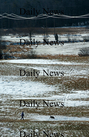 Amesbury:<br /> A person walks their dog at Woodsom Farm in Amesbury on Tuesday in a landscape almost free of snow, though that could change today as more snow is expected to blanket the area.<br /> Photo by Bryan Eaton/Newburyport Daily News Tuesday, January 06, 2009