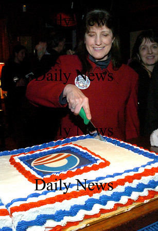 Newburyport:<br /> Pat Skibbee of C-10, a watchdog group of Seabrook Station, cuts a cake with Barack Obama's campaign logo at in inaugural party and fundraiser for the group at the Grog last night.<br /> Photo by Bryan Eaton/Newburyport Daily News Tuesday, January 20, 2009
