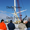 Newburyport:<br /> A crowd of about 20 people turned out to watch the rotor be lifted and attached to the housing atop the wind turbine being constructed at Mark Richey Woodworking in Newburyport's industrial park late Monday morning.<br /> Photo by Bryan Eaton/Newburyport Daily News Monday, January 12, 2009
