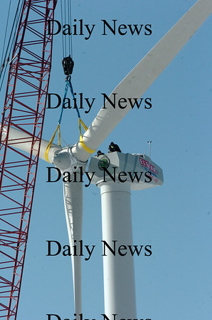 Newburyport:<br /> Workers atop the nacelle, or housing, of the wind turbine being constructed at Mark Richey Woodworking await as the rotor is lifted into place Monday.<br /> Photo by Bryan Eaton/Newburyport Daily News Monday, January 12, 2009