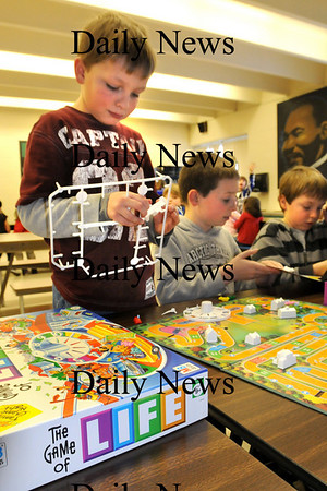 Amesbury:<br /> A.J. Carter, 10, with friends Evan Hangley, 9, Emmet Walsh, and Dane Webber, out of view, both 10, assembles a new Game of Life boardgame at the afterschool program at Amesbury Elementary School on Monday. It's one of the more popular games at the program, and the children were pleased to get the new game as the old one was worn out and missing pieces.<br /> Photo by Bryan Eaton/Newburyport Daily News Monday, January 26, 2009