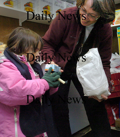 Amesbury:<br /> Joan Bukoskey, assistant director of Our Neighbor's Table, shows the contents of a healthy snack bag to Andrea Wall-Sanchez of Methuen. Our Neighbor Neighbor's received a grant to begin giving out healthy snack bags for children every Wendesday. The grant is funded by the Moseley Foundation and Merrimack Valley Food Bank.<br /> Photo by Bryan Eaton/Newburyport Daily News Wednesday, January 21, 2009