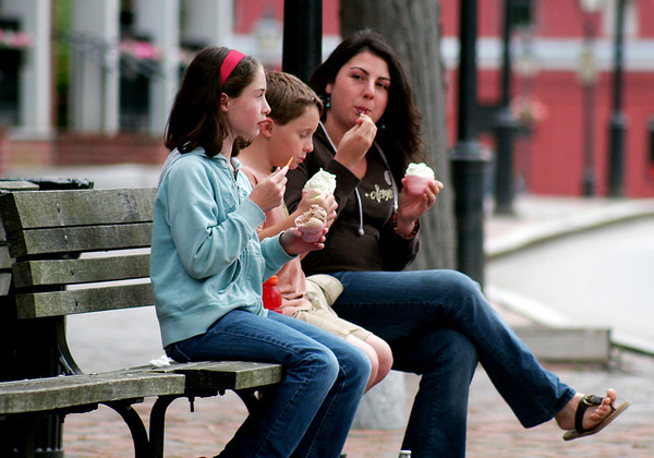Newburyport: Harry Blackman, his sister Olivia, and their baby sitter, Kendra Mclane, enjoy some ice cream on Market Square in Newburyport, despite the clouds and cool temperatures on Tuesday. Photo by Ben Laing/Staff Photo