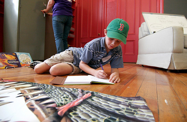 Newburyport: Sean Denner of Newburyport works on a drawing of dinosaur teeth in his journal while spending the day at the Kelley School as part of this summer's Youth Service programs. Photo by Ben Laing/Staff Photo