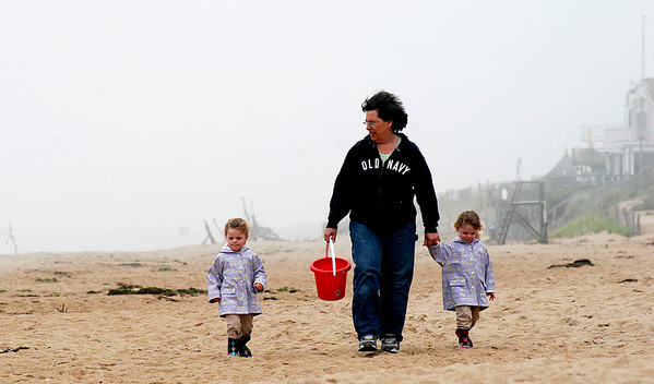 Newbury: Ainsley and Gabrielle Norris, 3 year old twin from Plum Island, and their nanny, Gail Allen, take a stroll along the beach collecting sea shells Tuesday afternoon. Photo by Ben Laing/Staff Photo