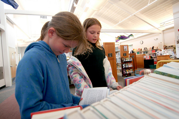 Byfield: Audrey Notargiacomo , left, of Salisbury, and Victoria Hackett, of Byfield, both 10, stop in at the Newbury Public Library Monday afternoon to check out some of the books in the childrens section. The pair walked to the library despite the rain and wind. Photo by Ben Laing/Staff Photo