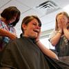 Newburyport: Tara Martin of Interlocks in Newburyport cuts eight inches of hair from Casey Barlowe, 14, of Newburyport, as her friend, Jessie Uhlig covers her eyes. Both were at Interlocks donating hair, along with fellow classmates, to a charity sponsored by Panteen. Photo by Ben Laing/Staff Photo