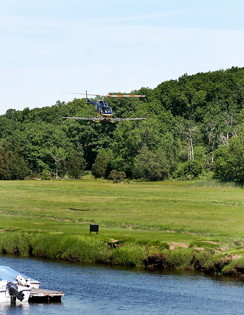 Newbury: A helicopter with equipment attached for spraying for mosquitos flies over the marsh along the Parker River in Newbury Wednesday morning. Photo by Ben Laing/Staff Photo