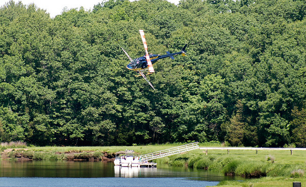 Newbury: A helicopter with equipment set up to spray for mosquitos banks sharply over the Parker River in Newbury Wednesday morning. Photo by Ben Laing/Staff Photo