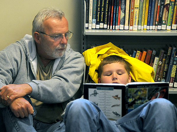 Newburyport: Ron Teel and his grandson Ron Teel, 9, read a boat about fish on a rainy Wednesday at the Newburyport Library. Jim Vaiknoras/staff photo