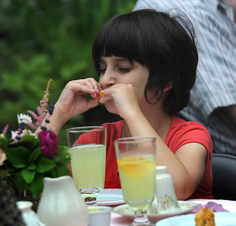 Amesbury:Hannah Daley, 7, enjoys an orange slice with her lemonaide at the Whittier home  in Amesbury for Tea in the Garden  Saturday morning. This was the first on four teas this summer, the other are July 16, August 12, and September 9.Jim Vaiknoras/Staff photo
