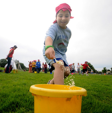 Danielle Harrison dumps her rice during a relay rice Survival Day at the Molin School Thursday. 4th and 5th graders emulated the TV show Survivor with 14 events testing the students skills and resolve. Jim Vaiknoras/staff photo