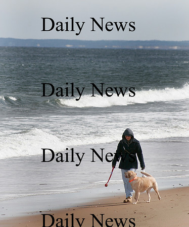 Newbury: Rebecca Shea of Rowley and her dog Cooper brave the cold and wind to take a walk on Plum Island Monday. Photo by Ben Laing/Staff Photo