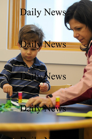 Merrimac: Ethan Sheehan and his mom Cathy work on a leprachaun hat during childrens storytime at the Merrimac Public Library Wednesday morning. Photo by Ben Laing/Staff Photo