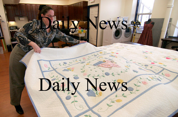 Amesbury: Jen Rodgers of Amesbury unfurls one of her great-grandmother hand made quilts at her shop, Crafters Quarters in downtown Amesbury. Photo by Ben Laing/Staff Photo