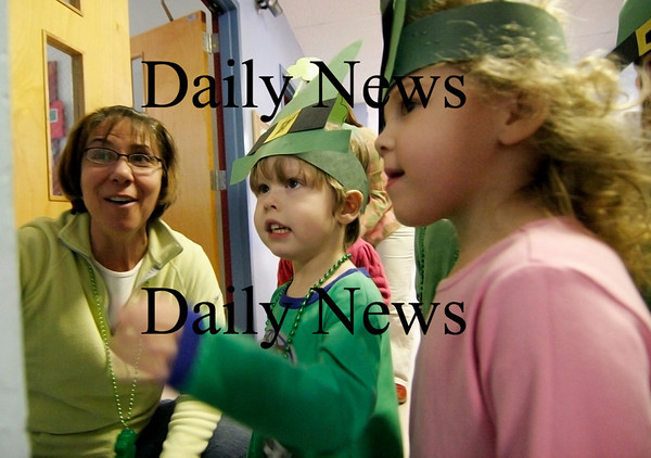 Rowley: Hayden Tracy, center, and Regan Golbitz, right, find a treat on their leprachaun hunt at the Pine Grove School in Rowley. Teacher Donna LaFlamme, left, led the pre-kindergarteners through the school looking for clues left by the leprachauns. Photo by Ben Laing/Staff Photo