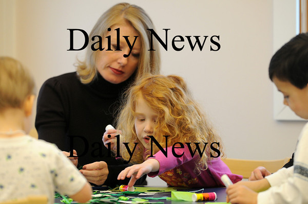 Merrimac: Jessica Baynes and her mom Nicola work on a leprachaun hat during children's storytime at the Merrimac Public Library on Wednesday morning. Photo by Ben Laing/Staff Photo