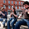 Newburyport: The Bowling siblings, Paddy, left, Meghan, center, and Tomas, right, all of Byfield, play traditional gaelic music in Market Square in Newburyport Monday. Ben Laing/Staff Photo