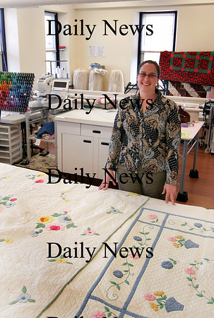 Amesbury: Jen Rogers, owner of Crafters Quarters in Amesbury, displays two hand made quilts created by her great-grandmother. Photo by Ben Laing/Staff Photo