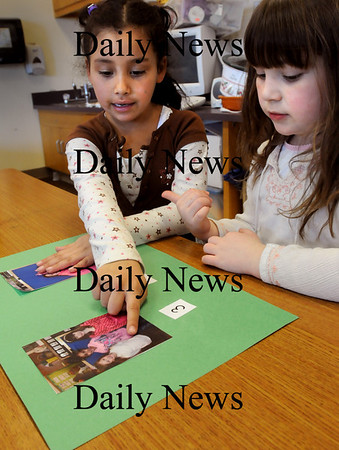 "Newbury:<br /> Mariana Murcia, left, and Anneliese Truesdale, both 6, work on their ""addition books"" in Jennifer Townsend's kindergarten class at the Newbury Elementary School on Thursday. Townsend took pictures of the children in various groupings and the children put the corresponding numerals underneath to add up how many children are on each page, helping them to visualize addition in a fun way.<br /> Photo by Bryan Eaton/Newburyport Daily News Thursday, March 12, 2009"