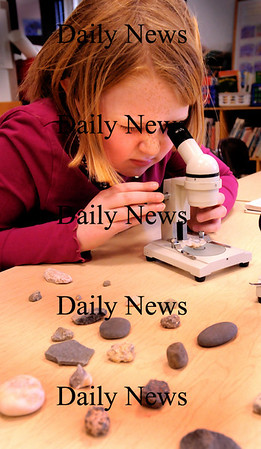 "Amesbury:<br /> Annika Welch, 8, compares a rock under a microscope with a reference guide as she tries to identify differents rocks from a collection her older brother gave her. She was in Peggy Laufer's class at Cashman Elementary School in Amesbury where the children were in ""plan it"" period where they planned different experiments and followed through with them.<br /> Photo by Bryan Eaton/Newburyport Daily News Monday, March 23, 2009"