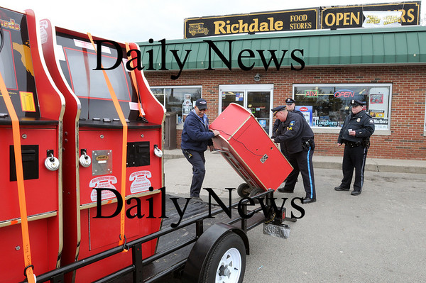 Salisbury:<br /> Salisbury Fire Dept. Lt. Tim Oliveira, left, and Sgt. Kevin Sullivan of the Salisbury Police Dept. roll one of two gaming machines allegedly used for illegal gambling at the Richdale in Salisbury Square onto a trailer. Several other businesses in town were raided as well, the machines already on the vehicle.<br /> Photo by Bryan Eaton/Newburyport Daily News Tuesday, March 31, 2009