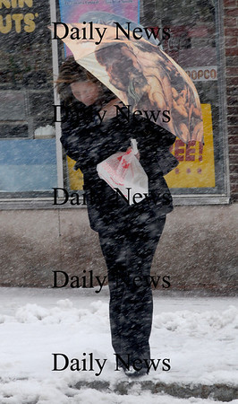 Newburyport:Tracey Hutchinson braces herself against the weather as she crosses State Street after picking up her lunch Monday. Jim Vaiknoras/Staff Photo