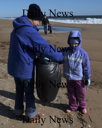 Newbury:Bella Lesinski, 7, puts some trash in a bag held by her mom Lauren during the Beach Clean up on Plum Island Saturday morning. Bella's dad Vinnie and sister Sophia, 3, are cleaning up in the back ground.Jim Vaiknoras/Staff photo