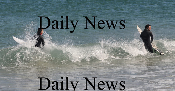 Salisbury: Derek Sidilou of Amesbury and Mike Haroutunian of Northwood take advantage of teh nice weather to surf on Salisbury Beach Sunday.photo by Jim Vaiknoras. Newburyport Daily News  Sunday March 8, 2009