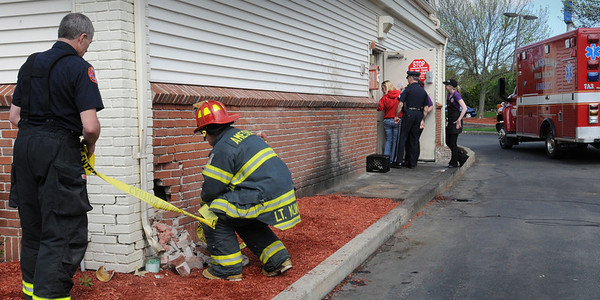 Amesbury: Amesbury firefighters put tape around the rear of Friendly's restaurant in Amesbury which was hit by a vehicle yesterday afternoon, just missing the gas meter, behind kneeling firefighter. Bryan Eaton/Staff Photo  Newburyport News  Wednesday May 6, 2009.