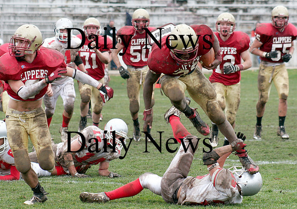 Newburyport: Josh Williams (39) is tripped up by Amesbury's Matt Enaire (25) as Newburyport hosted their rivals in their annual Thanksgiving Day football game. Newburyport shut out the Indians 33-0. Photo by Ben Laing/Staff Photo