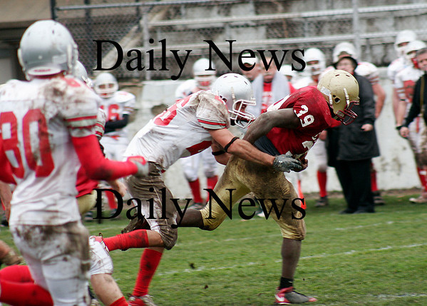 Newburyport: Josh Williams (39) tries to run through the tackle of Amesbury's Jesse Burrell (26) as Newburyport hosted their rivals in the annual Thanksgiving Day game. Newburyport shut out the Indians 33-0. Photo by Ben Laing/Staff Photo