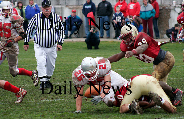 Newburyport: Amesbury's Jesse Burrell (26) fumbles the football after being hit by Newburyport's John Isabel (20) during the teams annual Thanksgiving Day game. Newburyport shut out the Indians 33-0. Photo by Ben Laing/Staff Photo