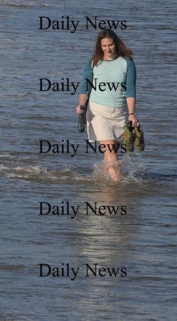 Newbury: Sacha Uljon takes advantage of the warm weather Sunday to stroll in the surf on Plum Island. Jim Vaiknoras/Staff photo