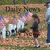 Newburyport: Kayla MacNeill, 9, and her grandfather Frank Marsolais of Salisbury, read the names of veterans on head stones at Veteran's Cemetery before the Veteran's Day Service their Wednesday morning. Jim Vaiknoras/Staff photo