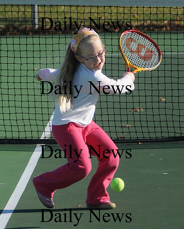 Newburyport:Becca Bloomberg, 6, of Exeter takes a cut at the ball while playing tennis with her brother Ryan, 9, at Cashman Park in Newburyport on a unseasonably warm Sunday afternoon. Jim Vaiknoras/Staff photo